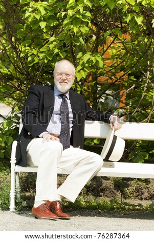 Happy older man taking a break in the park sitting in the shade on a bench - stock photo