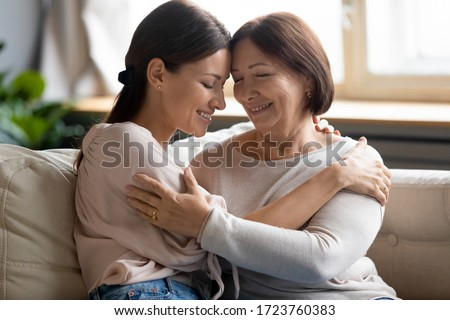 Happy older mother and adult daughter with closed eyes hugging, enjoying tender moment, sitting on couch at home, smiling young woman embracing mature mum, good trusted family relationship
