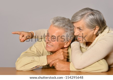Happy older pair on a light brown background