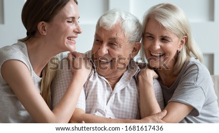 Happy older parents father and mother with adult daughter hugging close up, laughing at joke, chatting, sharing news, young granddaughter and mature grandparents having fun, spending weekend together Foto d'archivio ©