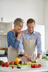 Happy older 60s vegan couple wearing aprons preparing healthy diet meal salad at home. Smiling mature senior family embracing, cooking together, cutting fresh organic vegetables together in kitchen.