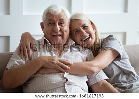 Happy older wife and husband hugging and laughing together, having fun, smiling mature father and adult middle-aged daughter sitting on cozy sofa at home, old couple enjoying tender moment