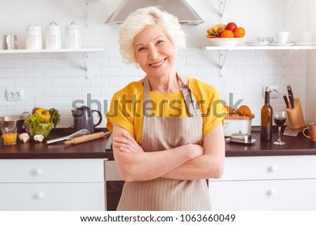 Happy older woman in apron preparing breakfast, crossed hands