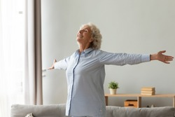 Happy older woman with toothy healthy smile standing with arms outstretched in living room at home, thankful grateful mature female feeling satisfied, doing easy exercises, stretching, enjoying life