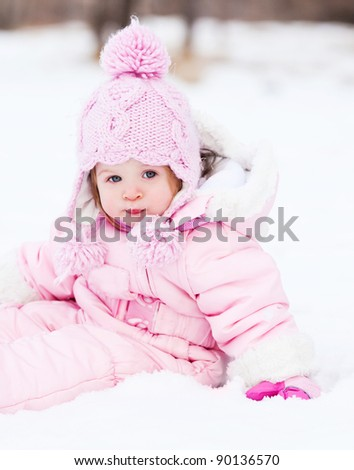 happy one year old baby girl  outdoor in the park  on a winter day