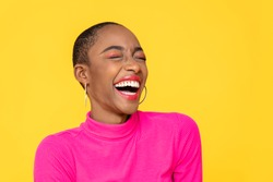Happy optimistic African American woman in colorful pink clothes laughing isolated on yellow background