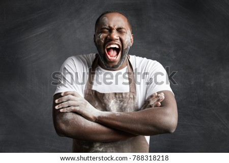 Happy overjoyed black male cook keeps hands crossed, laughs loudly at good joke of his colleague, keeps mouth widely opened and eyes closed, isolated over black chalk background. Emotions, occupation