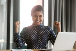 Happy overjoyed euphoric indian business woman winner celebrate online computer win, excited hindu girl professional student rejoice internet success victory professional triumph new job opportunity