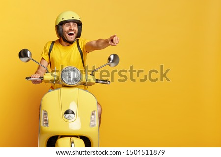 Happy overjoyed male rider points into distance, shows something great on road, wears protective headgear, yellow t shirt, poses on motorbike, copy space for your promotion, being on way home