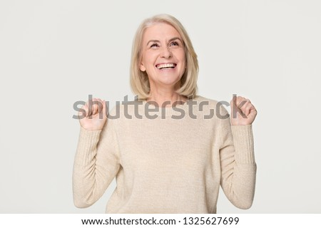 Happy overjoyed middle aged older woman celebrating fortune bid win victory success, excited euphoric lucky mature senior lady lottery winner rejoice triumph isolated on grey white studio background