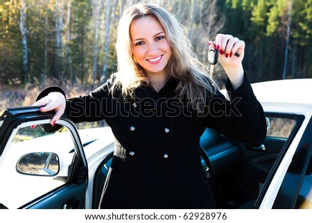 Happy owner of a new car showing a key.