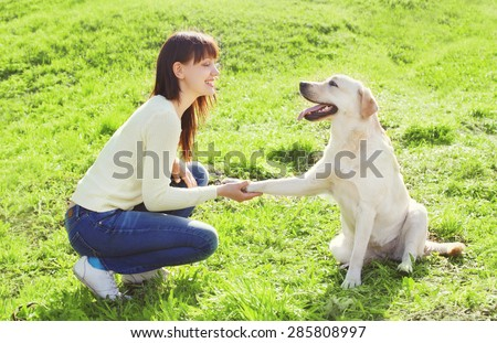 Happy owner woman with labrador retriever dog trains on the grass in summer day