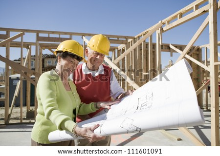 Happy owners reviewing blueprint on construction site