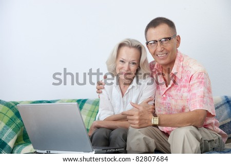 Happy pair on sofa with notebook