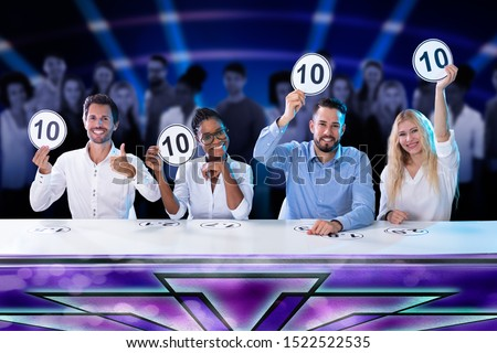 Happy Panel Judges Sitting In Front Of Red Curtain Showing 10 Score Signs ストックフォト ©