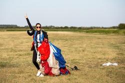 Happy parachute girl jumper after landing.