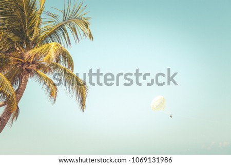Happy  Parasailing in exotix resort in summer. People under parachute hanging mid air. Having fun. Tropical Paradise.