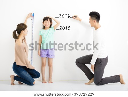 happy parent measures the growth of   daughter  #393729229