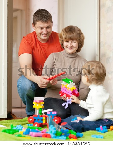 Happy parents and child plays with meccano set in home