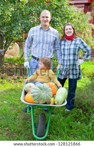 Happy parents and child with  harvested pumpkins in garden