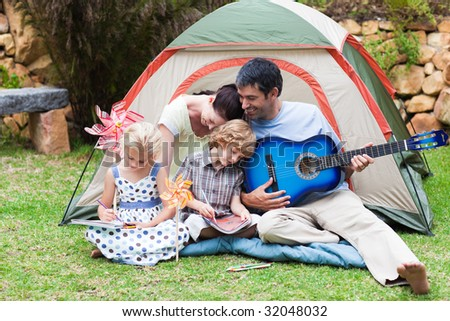 Happy parents and children playing a guitar in a tent