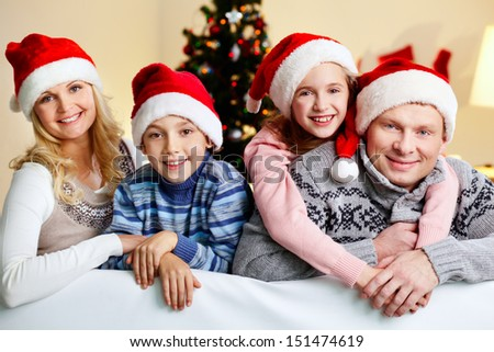 Happy parents and children sharing Christmas hugs