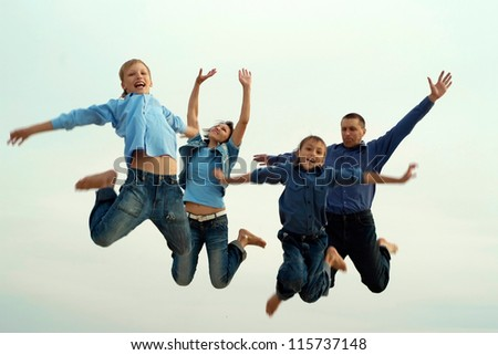 happy parents and children together in nature jump