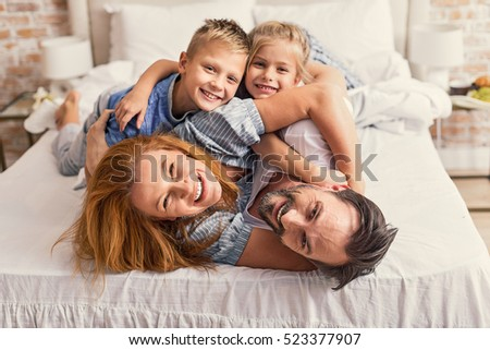 Happy parents and kids enjoying their morning in bed #523377907