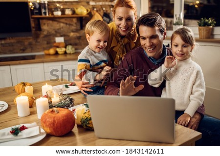Happy parents and kids using computer and waving while making video call berofe Thanksgiving dinner in dining room.