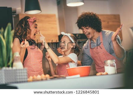 Happy parents and their daughter are preparing cookies together in the kitchen. Little girl is making fun putting some dough to mer mother nose.