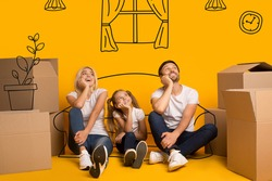 Happy parents and their kid with carton boxes imagining their new home on orange background with drawings
