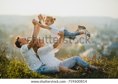 Happy parents and their little girl rest on the lawn in beautiful summer day #759600814