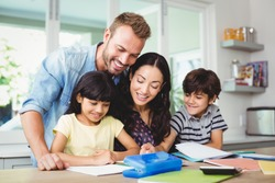 Happy parents assisting children doing homework at home