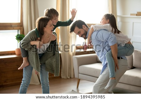 Happy parents carrying children on backs and running, family having fun at home, excited mother and father playing with adorable little son and daughter in modern living room, piggy back
