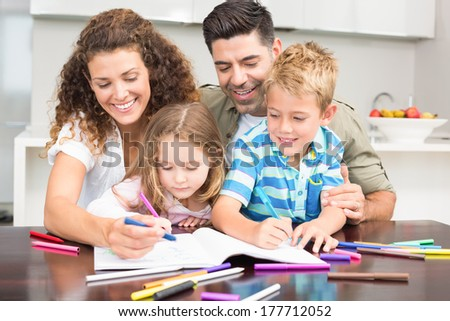 Happy parents colouring with their children at the table at home in kitchen