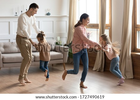 Happy parents dancing with little daughter in living room, excited mother and father holding cute preschool girls hands, moving to favorite music, spending weekend together, funny family activity