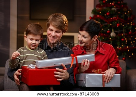 Happy parents giving christmas gifts to their son, smiling. ?