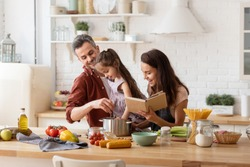 Happy parents helping daughter to cook. Mother with cookbook in hand, father with child on hand watching girl trying to catch something in pan. Family recreation and fun, loving relationships