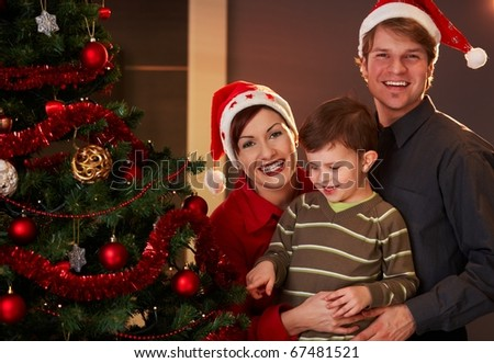Happy parents holding small child at christmas tree, boy pointing at tree.