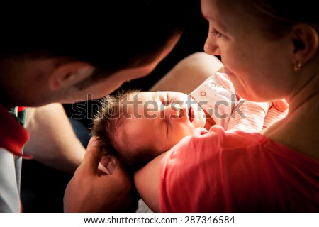 Happy parents holding their newborn baby girl