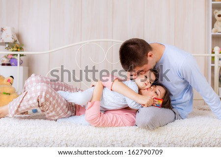 Happy parents kissing baby
