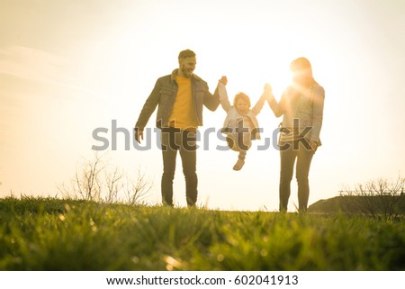 Happy parents playing with their daughter in the park. Space for copy.
