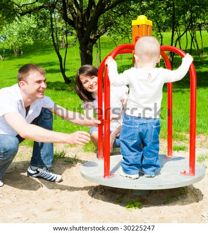 Happy parents rotating platform with their son