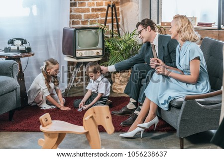 happy parents sitting on sofa and looking at little kids playing with domino tiles at home, 1950s style