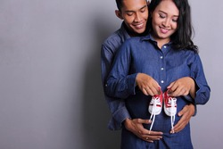 Happy parents-to-be couple looking at a cute red baby shoes for their unborn child, indoors studio portrait