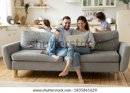 Happy parents using laptop, sitting on couch while kids playing funny game, smiling mother and father shopping online, enjoying leisure time, little son and daughter running and laughing together