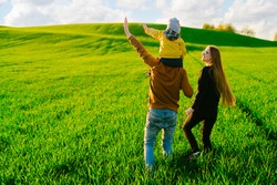 Happy parents with a young son walking on a field at sunset in the summer. Concept of family