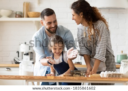 Happy parents with adorable little daughter having fun with dough, baking pastry or pie together, laughing father clapping hands with flour, overjoyed family enjoying leisure time in kitchen