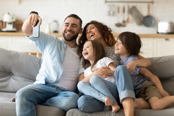 Happy parents with adorable little kids having fun, using mobile device, smiling father holding smartphone, taking selfie, overjoyed young family with daughter and son sitting on cozy couch at home