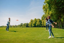 Happy parents with daughter playing with flying disk on green grass